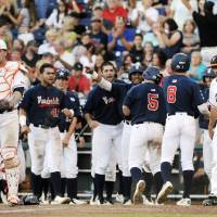 Photo - Virginia catcher Nate Irving, left, and pitcher Whit Mayberry (47) stand near as the Vanderbilt bench celebrates in the third inning of the opening game of the best-of-three NCAA baseball College World Series finals in Omaha, Neb., Monday, June 23, 2014. (AP Photo/Eric Francis)