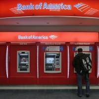 Photo - In this Dec. 13, 2012 photo, a customer stops at a Bank of America ATM office in Boston. Bank of America Corp. says it will spend more than $10 billion to settle mortgage claims resulting from the housing meltdown. Under the deal announced Monday, Jan. 7, 2013, the bank will pay $3.6 billion to Fannie Mae and buy back $6.75 billion in loans that the North Carolina-based bank and its Countrywide banking unit sold to the government agency from Jan. 1, 2000 through Dec. 31, 2008. That includes about 30,000 loans. (AP Photo/Charles Krupa)