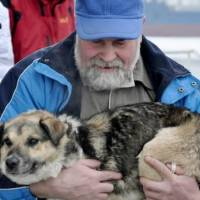 Photo - In this photo taken Tuesday, Jan. 26, 2010 and made available Thursday, Jan 28, 2010 Adam Buczynski carries a dog found floating cold and alone on an ice floe 15 miles off the Polish  Baltic  Sea coast in Gdynia, Poland. Buczynski, a sailor from the ship