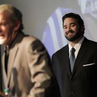 Photo - Jeff Saturday, right, listens to Indianapolis Colts owner Jim Irsay during a news conference before signing a one-day contract in order to retire as a Colts player, Thursday, March 7, 2013, in Indianapolis. Saturday spent 13 seasons in Indianapolis before signing with Green Bay last year. (AP Photo/AJ Mast)