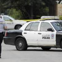 Photo - An Oklahoma City police investigator walks past an Oklahoma City police car riddled with bullet holes sitting on Miller Avenue just south of NW 39 Street Monday, August 30 ,2010. A female Oklahoma City police officer was shot in the car. Photo by Paul B. Southerland