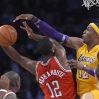 Photo - Los Angeles Lakers center Dwight Howard, right, blocks the shot of Milwaukee Bucks forward Luc Richard Mbah a Moute during the first half of an NBA basketball game, Tuesday, Jan. 15, 2013, in Los Angeles. (AP Photo/Mark J. Terrill)