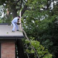 Photo - Bill Clements pushes a tree limb from his roof, with a little help from his wife Teri, who had a rope tied to it and pulled as Bill pushed, Monday, July 28, 2014, in Bloomfield Hills, Mich. Crews are working to restore power after series of severe thunderstorms hit Michigan's Lower Peninsula and knocked out power to more than 210,000 homes and businesses. The storms packed winds up to 70 mph that knocked down trees and ripped roofs off buildings. (AP Photo/Detroit News, Charles V. Tines)  DETROIT FREE PRESS OUT; HUFFINGTON POST OUT