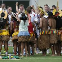 Photo - German's national soccer player Thomas Mueller, center, and his teammates visit with a group of Brazilian Indians who came to watch their training session, near Porto Seguro, Brazil, Monday, June 9, 2014. Germany will play in group G of Brazil's 2014 soccer World Cup. (AP Photo/Matthias Schrader)