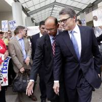 Photo - FILE - In an Aug. 19, 2014 file photo, Texas Gov. Rick Perry, front right, is escorted away from the Blackwell Thurman Criminal Justice Center, in Austin, Texas. Just when Perry was feeling like governor non grata, a felony indictment accusing him of abusing his power has energized Texas conservatives, who claim it's a politically motivated attack in an important election year. It's also put the spotlight back on Perry, who is trying to rehabilitate his political image before leaving office in January and convince would-be 2016 Republican primary voters across America he's worth a second look following an embarrassing White House bid three years ago. (AP Photo/Eric Gay, File)