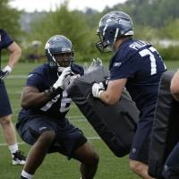 Photo - NFL FOOTBALL: In this photo taken on Friday, April 30, 2010, Seattle Seahawks first-round draft pick tackle Russell Okung, center left, squares off against rookie tackle Jacob Phillips, center right, as Mitch Erickson looks on at left, during rookie football mini-camp at Seahawks headquarters in Renton, Wash. (AP Photo/Ted S. Warren) ORG XMIT: WATW104