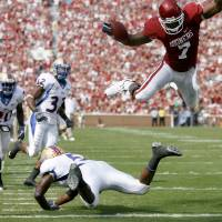 Photo - OU's DeMarco Murray leaps over Tulsa's DeAundre Brown for a touchdown during the first half of the college football game between The University of Oklahoma Sooners (OU) and the University of Tulsa Golden Hurricane (TU) at the Gaylord Family -- Oklahoma Memorial Stadium on Saturday, Sept. 19, 2009, in Norman, Okla.   Photo by Bryan Terry, The Oklahoman. ORG XMIT: KOD