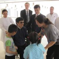 Photo -   In this photo released by the US Embassy Beijing Press Office, blind lawyer Chen Guangcheng, in wheel chair, meets his wife Yuan Weijing, right, daughter Chen Kesi, in blue shirt at second right, and son Chen Kerui, left, at a hospital in Beijing, Wednesday, May 2, 2012. U.S. ambassador to China, Gary Locke stands at Chen's right, and man at back in dark suit is language attache James Brown. (AP Photo/U.S. Embassy Beijing Press Office, HO)