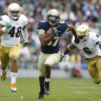 Photo -   Navy's Shawn Lynch, centre, tries to get past Notre Dame's Theo Riddick, right, during their NCAA college football game in Dublin, Ireland, Saturday, Sept. 1, 2012. (AP Photo/Peter Morrison)