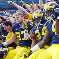 Photo - Michigan defensive end Brennen Beyer (97), defensive back Delonte Hollowell (24), and running back De'Veon Smith (4) celebrate in the stands with student fans after beating Appalachian State 52-14 in an NCAA college football game in Ann Arbor, Mich., Saturday, Aug. 30, 2014. (AP Photo/Tony Ding)