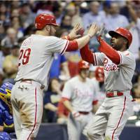 Photo - Philadelphia Phillies' Jimmy Rollins is congratulated by teammate Cameron Rupp after hitting a two-run home run during the sixth inning of a baseball game against the Milwaukee Brewers Wednesday, July 9, 2014, in Milwaukee. (AP Photo/Morry Gash)