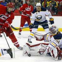 Photo - Carolina Hurricanes' Jordan Staal (11) charges into Buffalo Sabres goalie Michal Neuvirth (34), of the Czech Republic, during the second period of an NHL hockey game in Raleigh, N.C., Thursday, March 13, 2014. (AP Photo/Karl B DeBlaker)