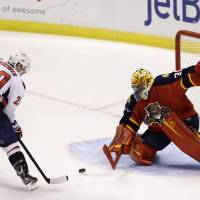 Photo - Washington Capitals right wing Troy Brouwer (20) scores a goal against Florida Panthers goalie Scott Clemmensen during an overtime period of an NHL hockey game, Tuesday, Feb. 12, 2013 in Sunrise, Fla. The Capitals defeated the Panthers 6-5 in overtime. (AP Photo/Wilfredo Lee)