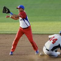 Photo - United States' Kyle Schwarber (44) steals second base against Cuba shortstop Yordan Manduley in the fourth inning of an exhibition baseball game in Papillion, Neb., Friday, July 19, 2013. (AP Photo/Nati Harnik)