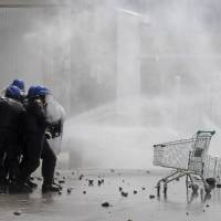 Photo - Amidst tear gas, police officers take cover from stones during clashes with looters at a supermarket in San Carlos de Bariloche, about 1.630 km southwest of Buenos Aires, Argentina, Thursday, Dec. 20, 2012. Hooded people looted at least three supermarkets and set a car on fire after claiming for food to celebrate Christmas in the city of Bariloche, part of Argentina's Patagonia region. (AP Photo/Diario Rio Negro)