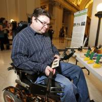 Photo - Philip Hampton looks at a modified garden tool during AgrAbililty Day at the State Capitol.  Steve Gooch - The Oklahoman