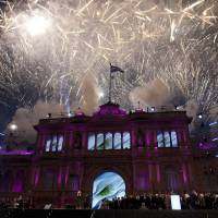 Photo - The government house is bathed in purple light as fireworks explode over a government rally in Buenos Aires, Argentina, Saturday, May 25, 2013. Cristina Fernandez's government and supporters are celebrating 10 years since she and her late husband Nestor Kirchner have held office, and the 203th anniversary of Argentina's May Revolution. (AP Photo/Natacha Pisarenko)