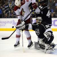 Photo - Phoenix Coyotes left wing David Moss, left, tries to get a shot in against Los Angeles Kings goalie Jonathan Quick, right, as defenseman Robyn Regehr helps defend during the first period of their NHL hockey game on Thursday, Oct. 24, 2013, in Los Angeles. (AP Photo/Mark J. Terrill)