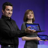 Photo - Mike Angiulo, corporate vice president of the Planning and PC Ecosystem team at Microsoft, shows the company's Surface tablet computer Thursday at the launch of Microsoft Windows 8 in New York. He is accompanied by Microsoft Vice President Julie Larson-Green. AP Photo
