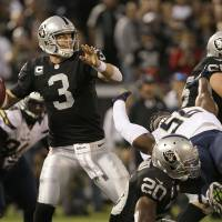 Photo -   Oakland Raiders quarterback Carson Palmer (3) passes as running back Darren McFadden (20) upends San Diego Chargers linebacker Donald Butler (56) during the first quarter of an NFL football game in Oakland, Calif., Monday, Sept. 10, 2012. (AP Photo/Jeff Chiu)