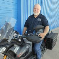 Photo -  Dan Maxey with the Yamaha Super Tenere motorcycle he rode to Alaska at his shop in Oklahoma City on Tuesday. Photo by Paul B. Southerland, The Oklahoman   PAUL B. SOUTHERLAND -  PAUL B. SOUTHERLAND