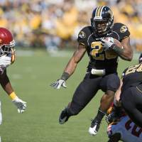 Photo - Missouri running back Henry Josey, center, leaps in the air as he tries to get past Iowa State's Jansen Watson, left, during the first half of an NCAA college football game Saturday, Oct. 15, 2011, in Columbia, Mo. (AP Photo/L.G. Patterson) ORG XMIT: MOLG102