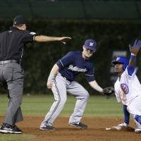 Photo - Chicago Cubs' Jorge Soler, right, asks for time from umpire Pat Hoberg, after sliding safely into second on a two-run double next to Milwaukee Brewers second baseman Scooter Gennetta during the third inning of a baseball game Wednesday, Sept. 3, 2014, in Chicago. (AP Photo/Charles Rex Arbogast)