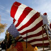 Photo - Volunteer David Burney from Milwaukee  helps put the finishing touches on the RDF TV rose float in Pasadena Monday, Dec. 31, 2012. (AP Photo/Nick Ut)