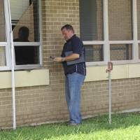 Photo -  An unidentified worker examines damage from an August 2013 underground water pipe break at Parker Intermediate School in McAlester.    Provided  -  Provided