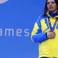 Photo - Ukraine's Olena Iurkovska covers her bronze medal with her hand after finishing third in the women's biathlon 12,5 km sitting during a medal ceremony at the 2014 Winter Paralympics, Friday, March 14, 2014, in Krasnaya Polyana, Russia. The majority of Ukraine's Paralympic medalists covered their medals during medal ceremonies. (AP Photo/Dmitry Lovetsky)