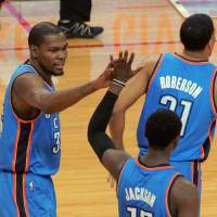 Photo - Oklahoma City Thunder forward Kevin Durant, left, high-fives teammate Reggie Jackson during the second half of an NBA basketball game against the Houston Rockets in Houston on Friday, April 4, 2014. Durant extended his streak of scoring at least 25 points to a 40th consecutive game, the longest streak since Michael Jordan reached 40 in 1986-87. The Rockets won 111-107. (AP Photo/Richard Carson)