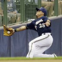 Photo - Milwaukee Brewers right fielder Gerardo Parra makes a falling catch on a ball hit by San Francisco Giants' Brandon Crawford during the eighth inning of a baseball game Tuesday, Aug. 5, 2014, in Milwaukee. (AP Photo/Morry Gash)