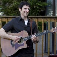 Photo - FILE - In this July 9, 2009 file photo, Musician Dave Carroll, of the pop-folk band Sons Of Maxwell, holds his repaired Taylor guitar in Halifax, Nova Scotia. Carroll became an Internet sensation after posting a revenge song about airline customer service on YouTube with his song