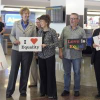 Photo - Oklahomans for Equality gather at Tulsa International Airport with their signs for a send off celebration in support for the plaintiffs in the Oklahoma Marriage Equality lawsuit as they head to the 10th Circuit Court of Appeals in Denver, Wednesday April 16, 2014. (AP Photo/Brandi Simons)