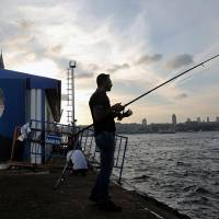 Photo - A man fishes near a billboard of Turkish Prime Minister Recep Tayyip Erdogan, in Istanbul, Turkey, Saturday, Aug. 9, 2014. Some 53 million Turks go the polls on Sunday to choose their 12th president in an election considered a turning point for the country of 76 million people, with Prime Minister Recep Tayyip Erdogan vying for the position he has pledged to transform from a symbolic role into a position of power. Ekmeleddin Ihsanoglu, the former chief of the Organization of Islamic Cooperation, and Kurdish politician Selahattin Demirtas are also running. (AP Photo/Emrah Gurel)