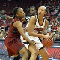 Photo - Louisville's Antonita Slaughter, right, looks to pass as Temple's Erica Coville defends during the first half of an NCAA college basketball game Wednesday, Feb. 12, 2014, in Louisville, Ky. (AP Photo/Timothy D. Easley)