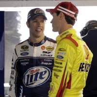 Photo - Drivers Brad Keselowski, left, and Joey Logano talk in the garage during practice for Sunday's NASCAR Sprint Cup series auto race at Martinsville Speedway in Martinsville, Va., Friday, April 5, 2013.  (AP Photo/Steve Helber)