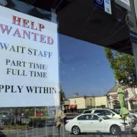 Photo - In  this , Friday, June 21, 2013, photo, a Help Wanted sign is displayed in the window of a restaurant at a shopping center in Charlotte, N.C.  The Labor Department reports on the number of Americans who applied for unemployment benefits last week on July 11, 2013. (AP Photo/Chuck Burton)