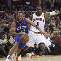 Photo - Philadelphia 76ers' Evan Turner (12) drives past Cleveland Cavaliers' C.J. Miles (0) during the first quarter of an NBA basketball game Saturday, Nov. 9, 2013, in Cleveland. (AP Photo/Tony Dejak)