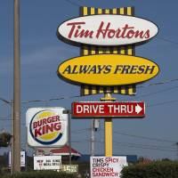 Photo - A Burger King sign and a Tim Hortons sign are displayed in Lower Sackville, Nova Scotia, Monday, Aug. 25, 2014. Burger King is in talks to buy Tim Hortons in hopes of creating a new, publicly traded company with its headquarters in Canada. (AP Photo/The Canadian Press, Andrew Vaughan)