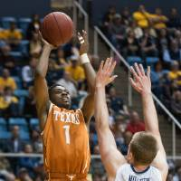 Photo - Texas' Isaiah Taylor, left, looks to shoot over West Virginia's Kevin Noreen during the first half of an NCAA college basketball game, Monday, Jan. 13, 2014, in Morgantown, W.Va. (AP Photo/Andrew Ferguson)