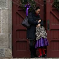 Photo - A woman hugs a young girl as they arrive for services at Trinity Church, Sunday, Dec. 16, 2012 in Newtown, Conn.  A gunman walked into Sandy Hook Elementary School in Newtown Friday and opened fire, killing 26 people, including 20 children. (AP Photo/Jason DeCrow)