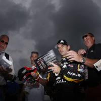 Photo - Jeff Gordon, center, signs autographs for fans after a practice session for Sunday's NASCAR Sprint Cup Series auto race at Pocono Raceway, Saturday, Aug. 2, 2014, in Long Pond, Pa. (AP Photo/Matt Slocum)