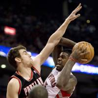 Photo - Toronto Raptors forward Amir Johnson, right, runs into defense from Portland Trail Blazers forward Victor Claver during the first half of an NBA basketball game in Toronto, Wednesday, Jan. 2, 2013. (AP Photo/The Canadian Press, Frank Gunn)