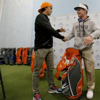 Photo - Former Oklahoma State golfer and current PGA pro Rick Fowler shakes hands with Moore tornado survivor Jake Rddington while Fowler makes a special appearance at Golfsmith in Oklahoma City, Okla. as a surprise to members for the three Moore school's golf teams, Monday, Jan. 6, 2014.  .Photo by Chris Landsberger, The Oklahoman