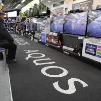 Photo - In this Jan. 31, 2013 photo, a shopper takes a look at Sharp's Aquos flat-panel TVs at an electronics store in Tokyo. Japanese electronics maker Sharp Corp. has reduced its quarterly losses but its outlook remains challenging. The Osaka-based company left its forecast for the full year ending March unchanged Friday, Feb. 1, at a 450 billion yen loss ($5 billion) as its flat-panel business for TVs and mobile devices gets hammered by plunging prices and intense competition. Sharp reported a 36.7 billion yen ($399 million) net loss for the October-December period, a smaller flow of red ink than its 173.6 billion yen loss a year earlier. It posted an operating profit for period, the first time in five quarters. (AP Photo/Shizuo Kambayashi)