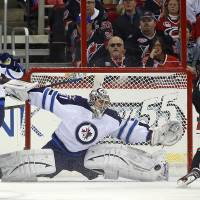 Photo - Carolina Hurricanes' Jiri Tlusty (19) of the Czech Republic has his shot blocked by Winnipeg Jets goalie Ondrej Pavelec (31) of the Czech Republic,  with Jets Zach Bogosian (44) nearby during the first period of an NHL hockey game, Tuesday, March 26, 2013, in Raleigh, N.C. (AP Photo/Karl B DeBlaker)