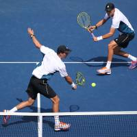 Photo - Mike Bryan, left, returns a shot as Bob Bryan looks on during a doubles match against Bradley Klahn, and Tim Smyczek, during the third round of the 2014 U.S. Open tennis tournament, Monday, Sept. 1, 2014, in New York. (AP Photo/John Minchillo)