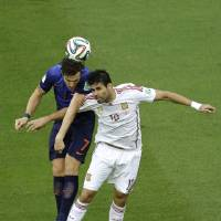 Photo - Spain's Diego Costa and Netherlands' Daryl Janmaat go for a header during the group B World Cup soccer match between Spain and the Netherlands at the Arena Ponte Nova in Salvador, Brazil, Friday, June 13, 2014.  (AP Photo/Christophe Ena)