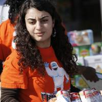 Photo - Lara Keddissi helps load food collected for the Regional Food Bank of Oklahoma.